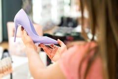 Femme tenant les talons hauts roses dans le magasin de chaussures photo libre de droits