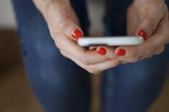 Femme tenant Smartphone avec Coral Nails Photographie stock libre de droits