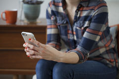 Femme tenant Smartphone dans une maison moderne Photos libres de droits