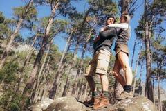 Femme tenant son associé masculin par derrière la position sur des roches Photos libres de droits
