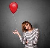 Femme tenant un ballon rouge Images stock