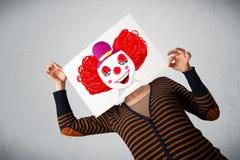 Femme tenant un carton avec un clown là-dessus devant son hea Photographie stock libre de droits