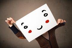 Femme tenant un carton avec un visage souriant là-dessus Photo libre de droits