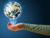 Femme tenant un globe rougeoyant de la terre Images stock