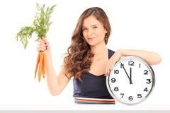 Femme tenant un groupe de carottes et d'une grande horloge murale Image stock