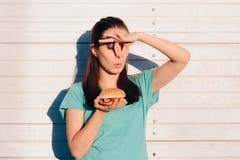 Femme tenant un hamburger Stinky et répugnant photographie stock