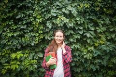 Femme tenant un livre vert et rouge Images libres de droits