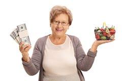 Femme tenant un panier à provisions et des piles d'argent Image stock
