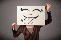 Femme tenant un papier avec le visage souriant mignon là-dessus devant He images libres de droits