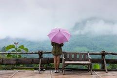 Femme tenant un parapluie sous la pluie Photos stock