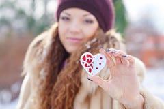 Femme tenant un peu de coeur en parc d'hiver photographie stock libre de droits