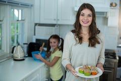 Femme tenant un plat des petits gâteaux tandis que sa fille préparant le petit déjeuner Photos stock