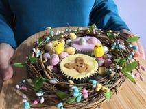 Femme tenant un plateau avec les petits gâteaux glacés orientés d'éponge de Pâques dans une guirlande de Pâques photo stock