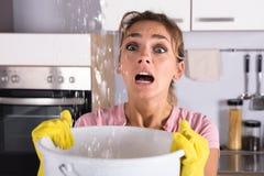 Femme tenant un seau tandis que les gouttelettes d'eau coulent du plafond photos stock