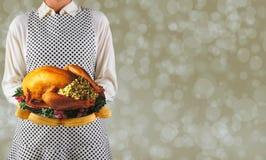Femme tenant un thanksgiving Turquie sur un plateau photos stock