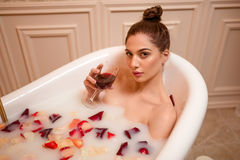 Femme tenant un verre de vin rouge dans le bain photo stock