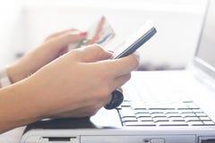Femme tenant une carte de crédit et un téléphone photos stock