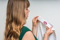 Femme tenant une chemise avec le rouge à lèvres de son mari infidèle Image libre de droits