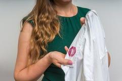 Femme tenant une chemise avec le rouge à lèvres de son mari infidèle Photo stock