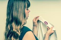Femme tenant une chemise avec le rouge à lèvres de son mari infidèle Image stock
