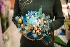 Femme tenant une composition en Noël dans le style marin fait d'arbre de sapin, boules en verre, coquillage, étoile de mer, masqu images libres de droits