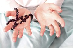 Femme tenant une croix avec des perles de chapelet photo stock