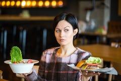 Femme tenant une salade et un hamburger Femme choisissant entre la consommation saine et malsaine Photographie stock