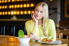 Femme tenant une salade et un hamburger Femme choisissant entre la consommation saine et malsaine Image libre de droits