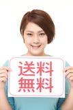Femme tenant une table des messages avec l'EXPÉDITION GRATUITE d'expression dans le KANJI Photo stock