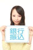 Femme tenant une table des messages avec le VIREMENT BANCAIRE d'expression dans le KANJI Photographie stock