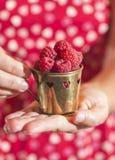 Femme tenant une tasse de framboises Photographie stock
