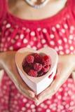 Femme tenant une tasse de framboises Photo libre de droits