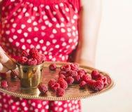 Femme tenant une tasse de framboises Image stock