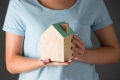 Femme tenant Wooden House modèle photographie stock