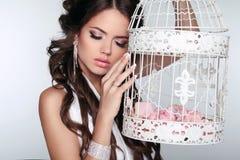 Femme tendre jugeant la cage à oiseaux de vintage d'isolement sur le backgrou gris Photos stock