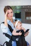 Femme tendue avec le bébé de transport de téléphone portable Photographie stock libre de droits