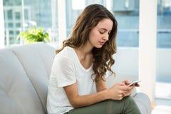Femme texting sur le sofa image libre de droits
