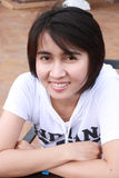 Femme thaï s'asseyant sur un banc Photo stock