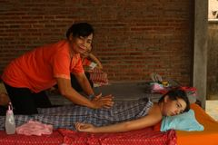 Femme thaïlandaise asiatique effectuant le massage au garçon européen d'adolescent photographie stock libre de droits