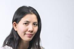 Femme thaïlandaise asiatique en gros plan souriant sur le fond blanc avec l'espace Photo stock