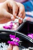 Femme tha?landaise faisant ? une tradition la guirlande tha?landaise de fleurs photo stock
