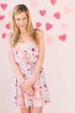 Femme timide avec les papiers en forme de coeur coincés contre Backgro coloré Photo libre de droits