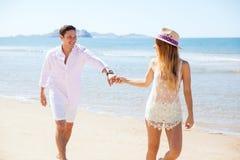 Femme tirant son ami pour une course à la plage Image libre de droits