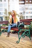 Femme étonnante s'asseyant sur un banc en dehors de lire un magazine, écoutant la musique, café délicieux potable Habillé dedans Images stock