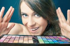 Femme étonnée avec la palette colorée pour le maquillage de mode Photographie stock libre de droits