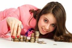 Femme touchant des piles de pièces de monnaie Photographie stock