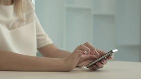 Femme touchant et passant en revue son téléphone intelligent images stock
