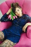 Femme très belle de mode avec les tulipes roses sur une chaise rose S image stock