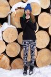 Femme très positive de jeunes dans le chapeau tricoté drôle bleu de chandail posant avec le thermos en hiver Forest Park contre d Photographie stock