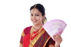 Femme traditionnelle tenant de nouvelles 2000 notes de roupie Photos stock